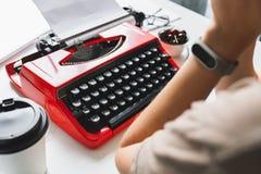 Συγγραφέας γυναικών που εργάζεται σκεπτικά σε ένα βιβλίο στην κόκκινη γραφομηχανή γραφείων της Στοκ Εικόνες