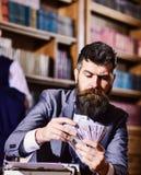 Συγγραφέας με το ακριβές πρόσωπο με τη γραφομηχανή στη βιβλιοθήκη με τα βιβλία στοκ φωτογραφίες