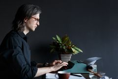 Συγγραφέας νεαρών άνδρων στο μαύρο πουκάμισο με μακρυμάλλη, στα γυαλιά που δακτυλογραφούν σε μια παλαιά γραφομηχανή σε έναν πίνακ στοκ εικόνα με δικαίωμα ελεύθερης χρήσης