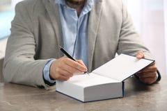 Συγγραφέας που υπογράφει το αυτόγραφο στο βιβλίο στον πίνακα στοκ εικόνες