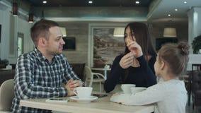 Συγκέντρωση της ευτυχούς οικογένειας στον καφέ πατέρας, μητέρα και κόρη που χαμογελούν και που κουβεντιάζουν από κοινού απόθεμα βίντεο