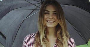 Συγκίνηση κινηματογραφήσεων σε πρώτο πλάνο ενός όμορφου ladie κάτω από το μεγάλο χαμόγελο ομπρελών απόθεμα βίντεο