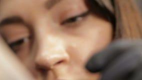 Συγκίνηση στο πρόσωπο και τα μάτια του όμορφου θηλυκού καλλιτέχνη δερματοστιξιών κατά τη διάρκεια της εργασίας απόθεμα βίντεο