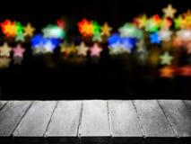 Συγκεκριμένη επιφάνεια μπροστά από τα ζωηρόχρωμα αστέρια bokeh στο σκοτεινό υπόβαθρο Στοκ Εικόνες