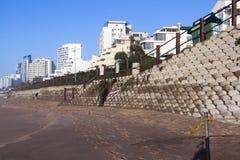 Συγκεκριμένος διατηρώντας τοίχος στην κενή παραλία ενάντια στον ορίζοντα πόλεων Στοκ εικόνα με δικαίωμα ελεύθερης χρήσης