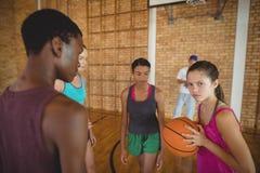 Συγκεντρωμένα παιδιά γυμνασίου που παίζουν την καλαθοσφαίριση Στοκ Φωτογραφία