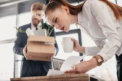 Συγκεντρωμένη επιχειρηματίας με τα έγγραφα και απολυθείς επιχειρηματίας με το κουτί από χαρτόνι πίσω Στοκ Εικόνες