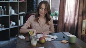 Συγκεντρωμένη επιχειρηματίας που εξετάζει έγγραφα με τα διαγράμματα και διαγράμματα τον πίνακα απόθεμα βίντεο