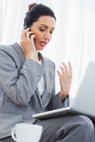Συγκεντρωμένη επιχειρηματίας που καλεί με το κινητό τηλέφωνό της και που χρησιμοποιεί τη συνεδρίαση lap-top στον καναπέ Στοκ Εικόνα
