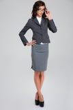 Συγκεντρωμένη επιχειρησιακή γυναίκα στα γυαλιά και το γκρίζο siut στοκ φωτογραφία