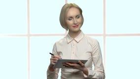 Συγκεντρωμένη επιχειρησιακή κυρία που εργάζεται στη συσκευή ταμπλετών φιλμ μικρού μήκους