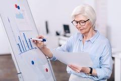 Συγκεντρωμένη ηλικίας επιχειρηματίας που χρησιμοποιεί το λευκό πίνακα στο γραφείο Στοκ φωτογραφία με δικαίωμα ελεύθερης χρήσης