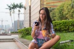 Συγκεντρωμένη νέα γυναίκα που δακτυλογραφεί ένα μήνυμα κειμένου στο κινητό τηλέφωνό της υπαίθρια Σοβαρό θηλυκό smartphone χρησιμο στοκ εικόνες