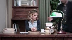 Συγκεντρωμένη νέα γυναίκα που διαβάζει ένα βιβλίο με ένα μολύβι στα χέρια της, που κάθονται σε ένα γραφείο όταν την φέρνει ο άνδρ απόθεμα βίντεο