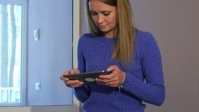 Συγκεντρωμένη νέα γυναίκα που χρησιμοποιεί την ταμπλέτα καθμένος στις αποσκευές της στο λόμπι ξενοδοχείων απόθεμα βίντεο