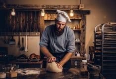 Συγκεντρωμένη να ζυμώσει αρχιμαγείρων ζύμη στην κουζίνα στοκ εικόνα