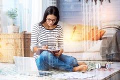 Συγκεντρωμένη πολυάσχολη γυναίκα που κάνει τις σημειώσεις στο σπίτι στοκ φωτογραφία