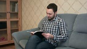 Συγκεντρωμένη συνεδρίαση βιβλίων ανάγνωσης νεαρών άνδρων στον καναπέ απόθεμα βίντεο