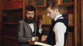 Συγκεντρωμένοι άνδρες σπουδαστές που διαβάζουν το εγχειρίδιο που αναλύει μαζί τις πληροφορίες Έξυπνοι νεαροί άνδρες που μιλούν γι απόθεμα βίντεο