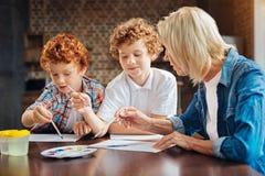 Συγκεντρωμένοι αδελφοί που χρωματίζουν με τη γιαγιά στο σπίτι Στοκ εικόνες με δικαίωμα ελεύθερης χρήσης
