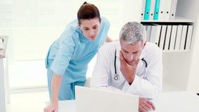 Συγκεντρωμένοι γιατροί που εξετάζουν το lap-top απόθεμα βίντεο