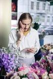 Συγκεντρωμένος ανθοκόμος που ελέγχει τη διαταγή του στο copybook στοκ φωτογραφίες