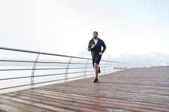 Συγκεντρωμένος αφρικανικός αθλητικός τύπος που τρέχει στην αποβάθρα το πρωί Στοκ Εικόνες