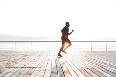 Συγκεντρωμένος αφρικανικός αθλητικός τύπος που τρέχει στην αποβάθρα το πρωί Στοκ Φωτογραφία