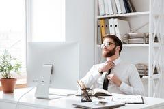 Συγκεντρωμένος επιχειρηματίας που εξετάζει τον υπολογιστή Στοκ Φωτογραφία