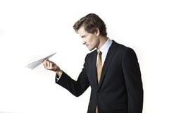 Συγκεντρωμένος επιχειρηματίας που εξετάζει το αεροπλάνο εγγράφου Στοκ Εικόνες
