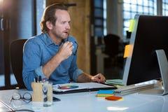 Συγκεντρωμένος επιχειρηματίας που εργάζεται στο γραφείο υπολογιστών Στοκ φωτογραφία με δικαίωμα ελεύθερης χρήσης