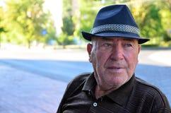 Συγκεντρωμένος ηληκιωμένος που φορά το καπέλο Στοκ Φωτογραφίες