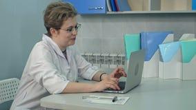 Συγκεντρωμένος θηλυκός γιατρός στα γυαλιά που δακτυλογραφεί στο lap-top στο γραφείο της Στοκ Εικόνα