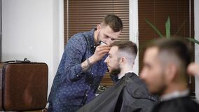 Συγκεντρωμένος κουρέας που χρησιμοποιεί trimmer κάνοντας το μοντέρνο hairdo στον πελάτη στο barbershop απόθεμα βίντεο