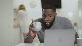 Συγκεντρωμένος λειτουργώντας φορητός προσωπικός υπολογιστής μαύρων στην ανοικτή κουζίνα απόθεμα βίντεο