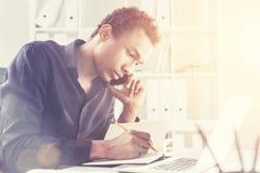 Συγκεντρωμένος μαύρος στο τηλέφωνο με το μολύβι Στοκ Εικόνες