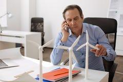 Συγκεντρωμένος μηχανικός που μιλά στο έξυπνο τηλέφωνο Στοκ εικόνα με δικαίωμα ελεύθερης χρήσης