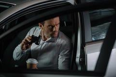συγκεντρωμένος μυστικός αρσενικός πράκτορας που κάνει την επιτήρηση από τις διόπτρες και που πίνει τον καφέ στοκ εικόνα με δικαίωμα ελεύθερης χρήσης