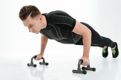 Συγκεντρωμένος νέος αθλητικός τύπος που κάνει την ώθηση UPS με τον εξοπλισμό γυμναστικής Στοκ Εικόνες