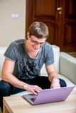 Συγκεντρωμένος νεαρός άνδρας με τα γυαλιά που λειτουργούν σε ένα γραφείο lap-top στο σπίτι Εξέταση την επίδειξη και χαμόγελο στοκ φωτογραφία