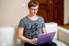 Συγκεντρωμένος νεαρός άνδρας με τα γυαλιά που λειτουργούν σε ένα lap-top σε ένα Υπουργείο Εσωτερικών Τύπος σε ένα πληκτρολόγιο κα στοκ εικόνα