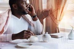Συγκεντρωμένος νεαρός άνδρας που εξετάζει το παράθυρο μιλώντας στο τηλέφωνο Στοκ Εικόνες