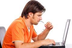 Συγκεντρωμένος νεαρός άνδρας που εργάζεται στο lap-top του Στοκ εικόνες με δικαίωμα ελεύθερης χρήσης