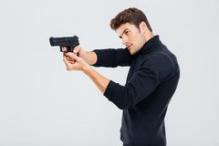 Συγκεντρωμένος νεαρός άνδρας που στέκεται και που στοχεύει με το πυροβόλο όπλο Στοκ εικόνα με δικαίωμα ελεύθερης χρήσης