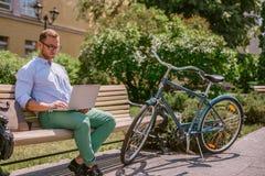 Συγκεντρωμένος περιστασιακός επιχειρηματίας που εργάζεται με το lap-top σε ένα διάλειμμα Στοκ Εικόνες