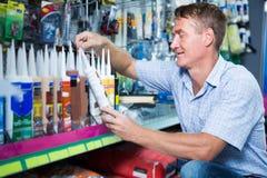 Συγκεντρωμένος πελάτης ατόμων που επιλέγει το σωλήνα στεγανωτικής ουσίας στην υπεραγορά Στοκ φωτογραφία με δικαίωμα ελεύθερης χρήσης