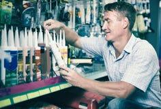 Συγκεντρωμένος πελάτης ατόμων που επιλέγει το σωλήνα στεγανωτικής ουσίας στην υπεραγορά Στοκ φωτογραφίες με δικαίωμα ελεύθερης χρήσης