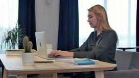 Συγκεντρωμένος στην εργασία, βέβαια νέα γυναίκα στην έξυπνη περιστασιακή ένδυση που λειτουργεί στο lap-top καθμένος κοντά στο παρ φιλμ μικρού μήκους