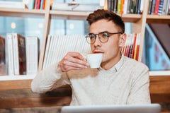 Συγκεντρωμένο άτομο που φορά τα γυαλιά που πίνουν τον καφέ Στοκ Φωτογραφία