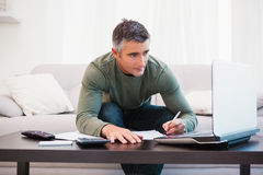 Συγκεντρωμένο άτομο χρησιμοποιώντας το lap-top και παίρνοντας τις σημειώσεις Στοκ Φωτογραφίες